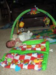 Nicholas rolling over and out of his playmat