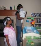 Rashida and Aminah tending to newborn Nicholas