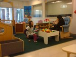 Akilah standing at play table in Infant 2 classroom